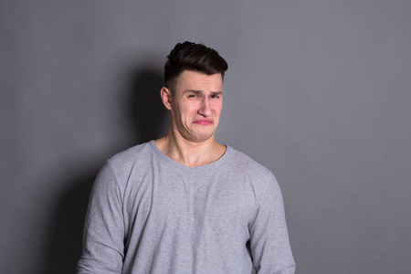Negative human emotion. Man expressing disgust on face, grimacing on grey studio background Stock Photo