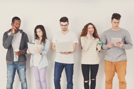 application university: Modern education. Diverse students using gadgets, standing in line on white studio background indoors, copy space