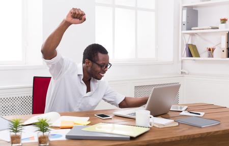 achievment: Happy businessman celebrate, win. Winner, black man in office with laptop