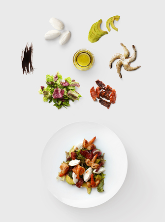 Cooking healthy food, seafood salad, isolated on white. King prawn, shrimps, lettuce, avocado, mozzarella and other ingredients near plate with dish