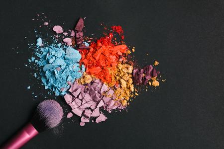 crushing: Beauty, makeup cosmetics. Eyeshadow splash palette and brush, colorful crushed eye shadow powder, flat lay, top view, black background