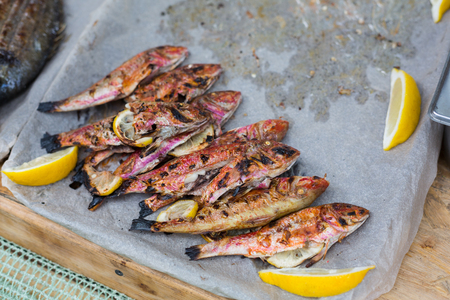 fish vendor: Red mullet grilled at barbecue. Seafood bbq outdoors at picnic, party. Street food vendor makes take away on big tray. Grill crispy roasted fish with lemon