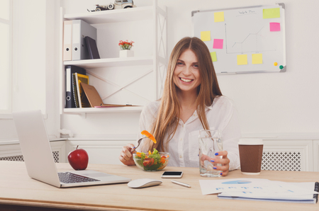 Woman has healthy business lunch in modern office interior. Young beautiful businesswoman at working place, eating vegetable salad in bowl, diet and vegetarian nutrition concept. Stock Photo