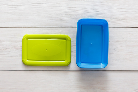 Empty plastic lunch boxes on white wood, top view. Green and blue containers