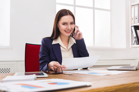 answer: Business consulting. Young businesswoman talking by phone at modern office workplace