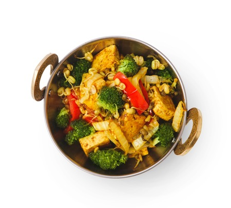 Restaurant vegan dish, tofu stir fry in copper bowl isolated on white, top view. Stock Photo