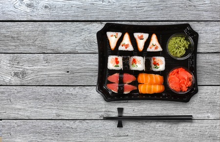 philadelphia: Japanese food delivery. Sushi and rolls top view with copy space on gray wood