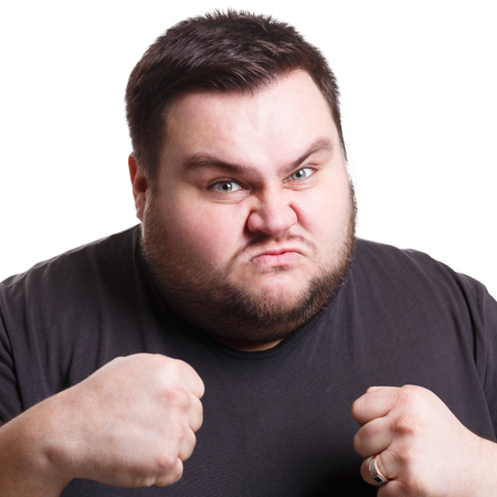 unprofessional: Furious angry fat man holding fists clenched, expressing anger, white isolated studio background Stock Photo