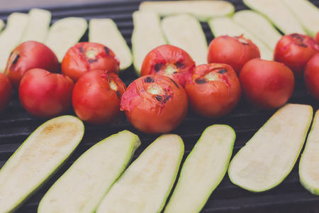 Vegetable vegan barbecue roasted on metal grill grate. Diet bbq. Zucchini and tomatoes closeup at picnic outdoors Stock Photo