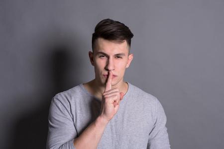 Secret, mystery. Hush sign showed by young man at gray studio background Reklamní fotografie