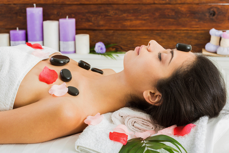 warming therapy: Black marble stone massage in ayurvedic spa. Beautiful girl in wellness center. Professional relaxation procedure to attractive young indian girl in beauty parlor.