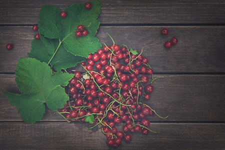Fresh ripe red currants heap on rustic wood background. Natural organic berries with green leaves scattered on weathered grey wooden table. Vintage dark filter Imagens