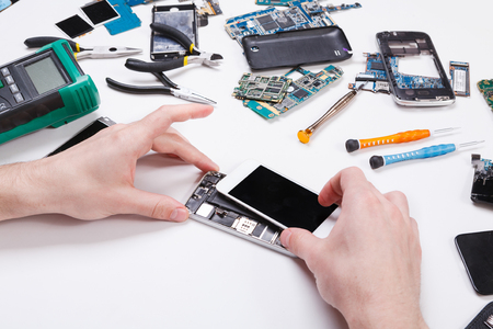 Electronics repair service. Repairman disassembling smartphone for inspecting. Technician fixing broken phone, copy space for text Banco de Imagens - 78700171