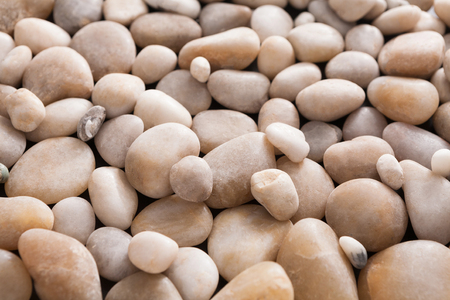 beige: Sea pebbles background. Natural seashore stones textured surface, selective focus, shallow depth of field