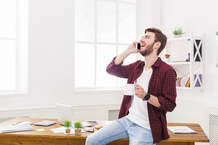 Happy and relaxed businessman in casual talk mobile in office. Young businessman in casual has phone talk in modern workplace interior.