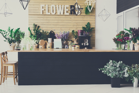 Small business. Flower shop interior. Floral design studio, decorations and arrangements. Flowers delivery service and sale of home plants in pots, wooden showcase, filtered image Stockfoto