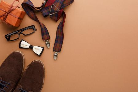 与男性衣裳的愉快的父亲节卡片礼物,鞋子和其他人的东西在黄柏纹理背景