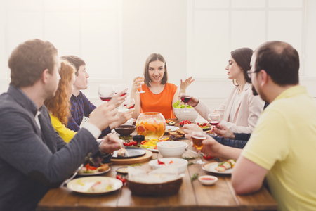 Friends have party dinner in cafe, restaurant. Young company celebrate with alcohol and food at wooden table indoors. Imagens