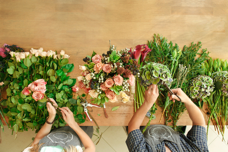 retailer: Small business. Flowers delivery top view. Florists creating order, making rose bouquet in flower shop.