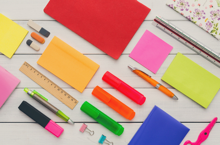 Flat lay of office and school stationery supplies - set of colorful markers, sticky notes, notepads, pens, rulers and erasers on white wooden table background, top view, nobody, objects Stock Photo