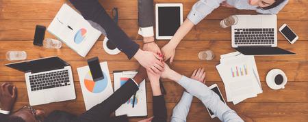 Multi-etnisch team stelt het concept van handen, verbinding, teambuilding en alliantie samen. Mensen op kantoor, jonge zakenlui en -vrouwen verenigen handen voor teamwerk en samenwerking. Bovenaanzicht, overhead