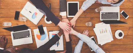 Multiethnic Team put hands together, connection, teambuilding and alliance concept. People in the office, young businessmen and women unite hands for teamwork and cooperation. Top view, overhead Фото со стока