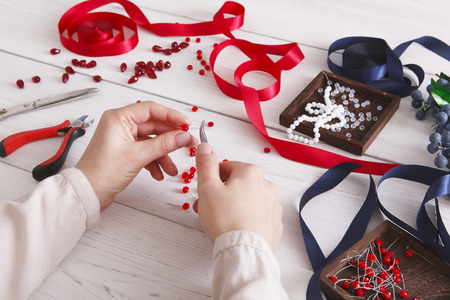 Woman making jewelry, home workshop. Artisan pov, female hands creating accessory with beads and ribbons. Beauty, creativity, handicraft concept
