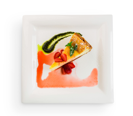 Restaurant dessert, cheesecake with fresh strawberries and mint sauce at square plate isolated, top view