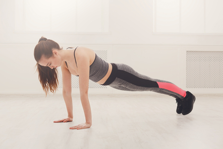 Fitness woman plank workout training at white background indoors. Young slim girl makes exercise. Stock Photo