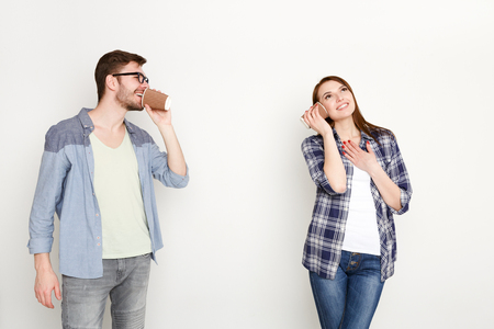 Communication and fun. Young casual couple talking through tin can phone, isolated on white background Standard-Bild