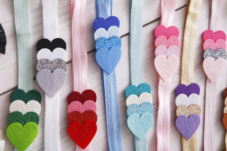 Reeks kleurrijke elastiek verfraaide hoofdbanden. Heldere handgemaakte haaraccessoires met decoratie van vilten harten. Schoonheid, mode, stijlconcept