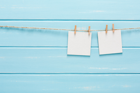 paper pin: White blank cards on rope, blue wooden background. Creative reminder, small sheets of paper on clothespin, bright memo backdrop Stock Photo