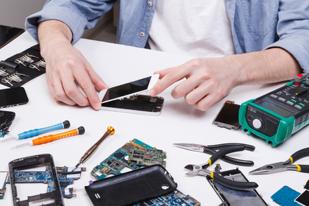 Repairman disassembling smartphone for inspecting. Technician fixing broken phone, electronics repair service 免版税图像