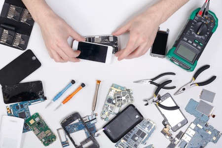 Cell phone repair at service center, smartphone dissasembling and diagnostic, repairman workplace top view
