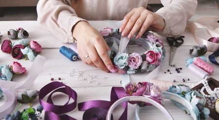 Handmade headbands making, home workshop. Unrecognizable woman artisan decorating hair hoop with flowers and ribbons. Art, handicraft, creative concept