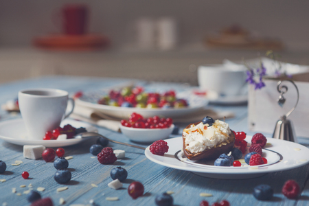 mascarpone: Sweet breakfast with baked pea and mascarpone dessert and berries - red currant, raspberry and bluberries. Beautiful food served at blue rustic wooden table, dish at white porcelain plate, coffee cup.