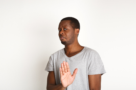 Black man expressing disapprovement, rejecting hand gesture, on white studio background. Negative emotions