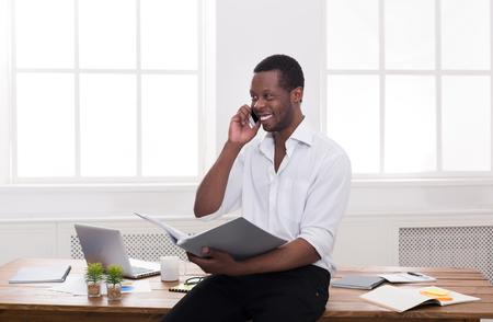 koncentrovaný: Černý podnikatel s papíry a mobilní. Mladý muž diskutuje o dokumentech na mobil v moderní kanceláři, kopírovat prostor Reklamní fotografie