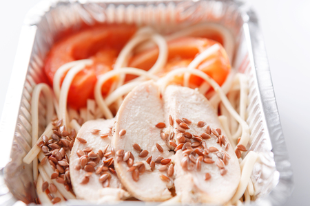 Healthy lunch in foil container. Fitness menu take away and delivery. Durum wheat pasta, steamed turkey, fresh vegetables and flax seeds in box on white background, closeup Stock Photo