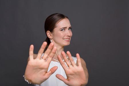고마워하지만 아니오를 말하는 매력적인 여자. 아름 다운 소녀 그녀의 손으로 중지 제스처를 만드는 제안을 부정, 카메라를 찾고 스톡 콘텐츠