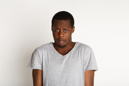 shoked: Negative emotions. Black man expressing fear and hesitation, standing on white background, studio shot