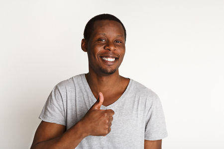 Ich mag das. Glücklicher schwarzer Mann, der Daumen herauf Geste zeigt und auf weißem Hintergrund, Atelieraufnahme lächelt