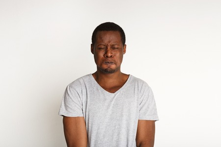 Black man expressing fear and disgust on face, grimacing on white studio background. Negative emotions