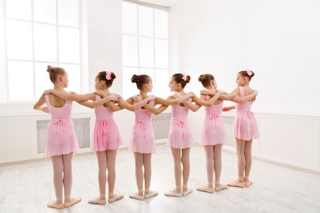 Little girls dancing ballet in studio. Choreographed dance by a group of graceful pretty young ballerinas practicing during class Banco de Imagens
