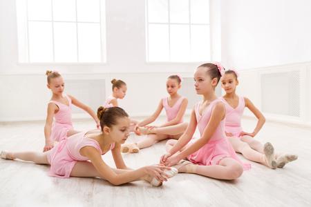 Jonge ballerina's die zich vóór prestaties, klassieke dansschool uitrekken