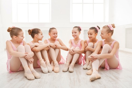 Kleine Ballerinen sprechen im Ballettstudio. Gruppe von Mädchen mit Pause in der Praxis, sitzen auf dem Boden. Klassische Tanzschule