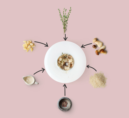 Risotto with wild mushrooms ingredients flat lay, isolated on pink background. Rice, fungus, sauce, parmesan and other ingredients around plate with dish ready Stock Photo