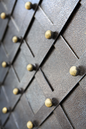 smithy: Vintage metallic pattern of medieval gate. Decorative grunge checkered iron structure background. Architectural detail vertical image, selective focus Stock Photo