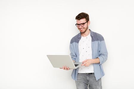 Junger Mann, der mit Laptop steht. Hübscher Kerl in den Gläsern, die offenes Notizbuch in seiner Hand und in der Arbeit an ihm halten. Information, Technologiekonzept