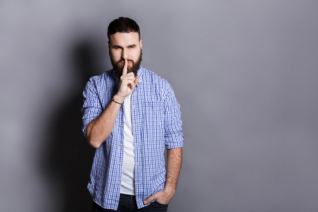 rumour: Bearded man shows hush be quiet. Handsome guy holding finger at his lips, gray studio background, copy space. Secret, privacy concept